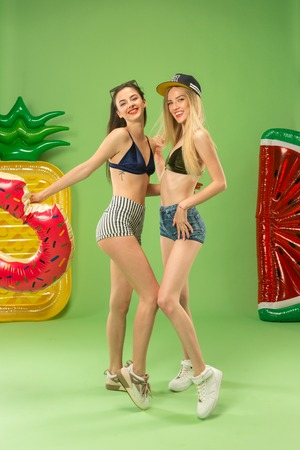 Cute girls in swimsuits posing at studio. Summer portrait caucasian teenagers on green background.