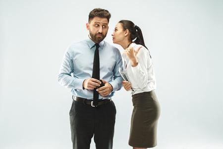 La giovane donna che bisbiglia un segreto dietro la sua mano su sfondo bianco