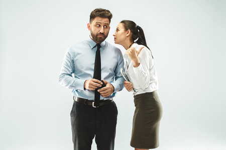 La joven susurrando un secreto detrás de su mano sobre fondo blanco.