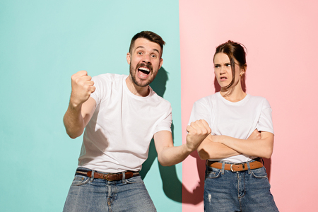 Closeup portrait of young couple, man, woman. One being excited happy smiling, other serious, concerned, unhappy on pink and blue background. Emotion contrasts Stock Photo - 104705562