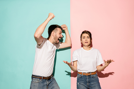 Closeup portrait of young couple, man, woman. One being excited happy smiling, other serious, concerned, unhappy on pink and blue background. Emotion contrasts Stock Photo - 104705567
