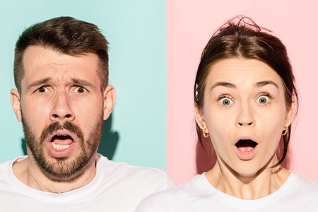 Closeup portrait of young couple, man, woman. One being excited happy smiling, other serious, concerned, unhappy on pink and blue background. Emotion contrasts