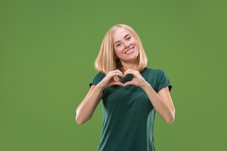 Portrait of attractive cute girl with kiss isolated over green background
