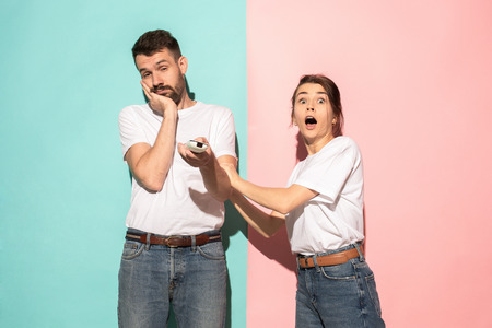 Closeup portrait of young couple, man, woman. One being excited happy smiling, other serious, concerned, unhappy on pink and blue background. Emotion contrasts Stock Photo - 104245103