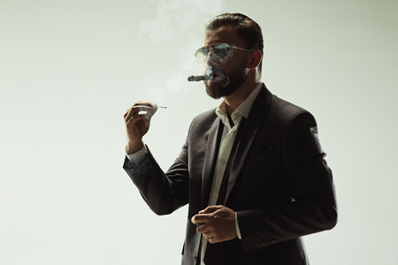 The barded man in a suit holding cigar Archivio Fotografico - 104285432