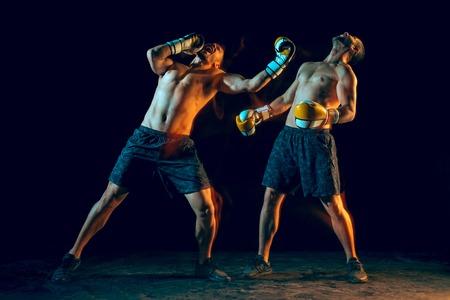 Male boxer boxing in a dark studio Stock Photo - 104440764