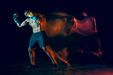 Male boxer boxing in a dark studio Stock Photo - 104440770