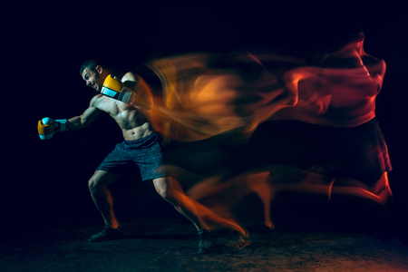 Male boxer boxing in a dark studio Stock Photo - 104440776