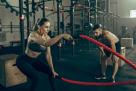 Woman with battle ropes exercise in the fitness gym. 스톡 콘텐츠