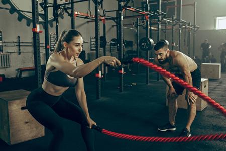 Donna con funi di battaglia esercizio in palestra.