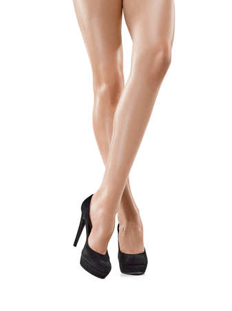 Gebräunte weibliche Beine in den hohen Absätzen lokalisiert auf weißem Hintergrund. Standard-Bild
