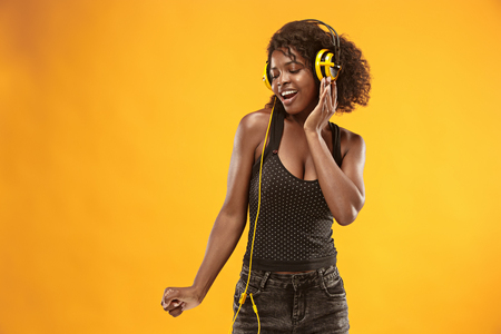 Studio portrait of adorable curly girl happy smiling during photoshoot. Stunning african woman with light-brown skin relaxing in headphones Фото со стока