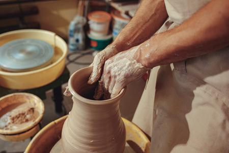 Creating a jar or vase of white clay close-up. Master crock. Man hands making clay jug macro.