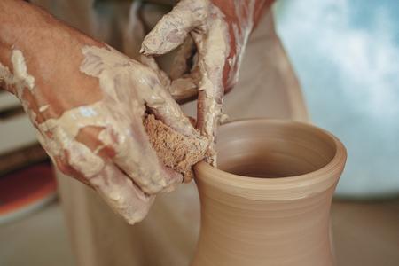 Creating a jar or vase of white clay close-up. Master crock. Man hands making clay jug macro. Stock Photo - 105404352