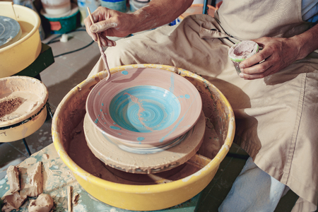 Creating a jar or vase of white clay close-up. Master crock. Man hands making clay jug macro. Stock Photo - 105404356