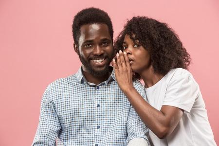 La joven susurrando un secreto detrás de su mano al hombre afro