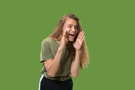 Isolated on green young casual woman shouting at studio 写真素材