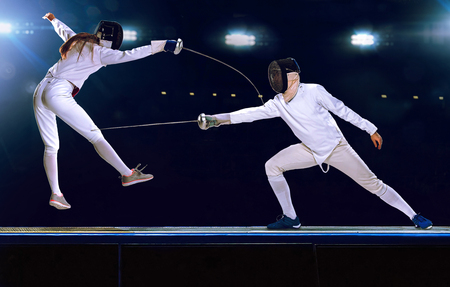 Two fencing athletes fight on professional sports arena 스톡 콘텐츠