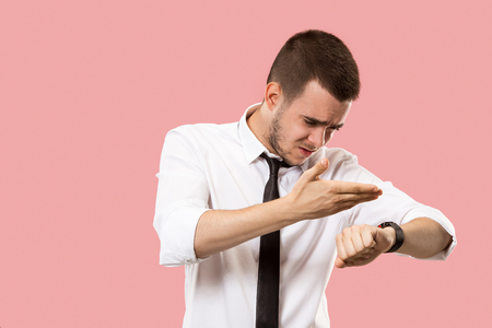 Handsome businessman checking his wrist-watch Isolated on pink background