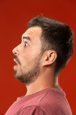 The young attractive man looking suprised isolated on red