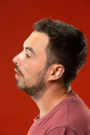 Beautiful man looking suprised and bewildered isolated on red