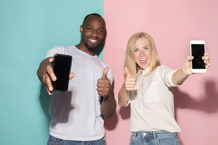 Portrait of a confident casual girl showing blank screen mobile phone and afro man Zdjęcie Seryjne