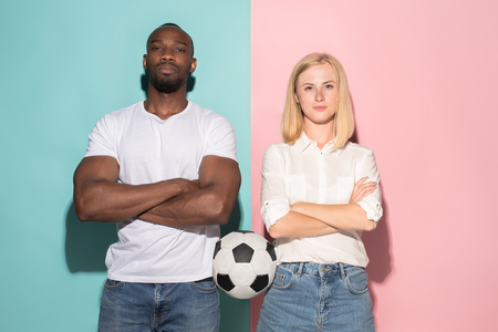 Closeup portrait of young couple, man, woman with football ball. They are serious, concerned on pink and blue background. Stock Photo - 105282996