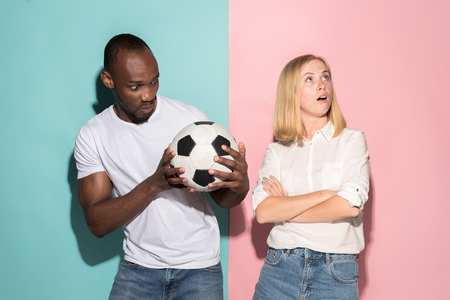 Closeup portrait of young couple, man, woman with football ball. They are serious, concerned on pink and blue background.