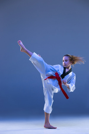 Young girl training karate on blue background Zdjęcie Seryjne