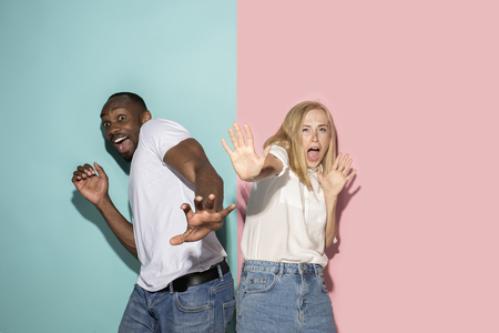 Portrait of the scared couple on pink and blue studio background