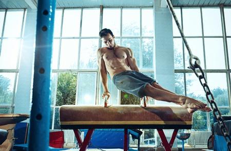 The sportsman during difficult exercise, sports gymnastics Foto de archivo - 105653697
