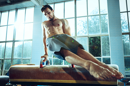 The sportsman during difficult exercise, sports gymnastics Foto de archivo - 105653700