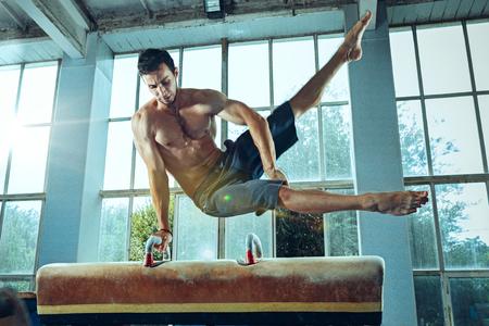 The sportsman during difficult exercise, sports gymnastics Foto de archivo - 105653707