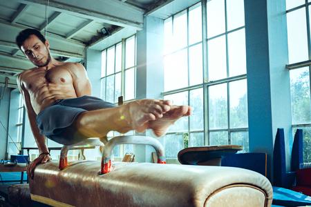 The sportsman during difficult exercise, sports gymnastics Foto de archivo - 105653717