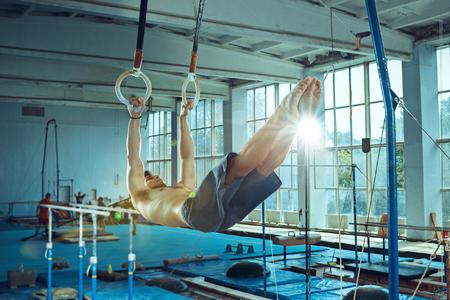 The sportsman during difficult exercise, sports gymnastics Foto de archivo - 105653731