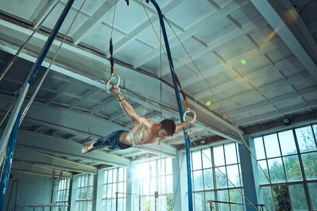 The sportsman during difficult exercise, sports gymnastics Foto de archivo - 105653734