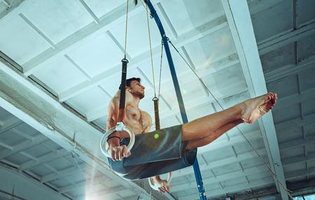 The sportsman during difficult exercise, sports gymnastics Foto de archivo - 105653737