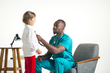 The healthcare and medical concept - african male doctor with stethoscope listening to child chest in hospital. The doctor, health, medicine, patient, pediatrician, illness concepts