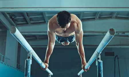The sportsman performing difficult gymnastic exercise at gym. The sport, exercise, gymnast, health, training, athlete concept. Caucasian fit model Foto de archivo - 105818659