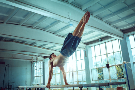 The sportsman performing difficult gymnastic exercise at gym. The sport, exercise, gymnast, health, training, athlete concept. Caucasian fit model Foto de archivo - 105818656