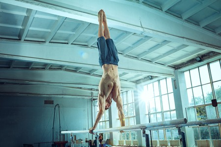 The sportsman performing difficult gymnastic exercise at gym. The sport, exercise, gymnast, health, training, athlete concept. Caucasian fit model Foto de archivo - 105909234
