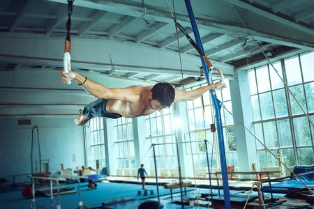 The sportsman performing difficult gymnastic exercise at gym. The sport, exercise, gymnast, health, training, athlete concept. Caucasian fit model Foto de archivo - 105909237