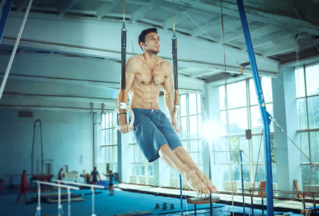 The sportsman performing difficult gymnastic exercise at gym. The sport, exercise, gymnast, health, training, athlete concept. Caucasian fit model Foto de archivo - 105909238