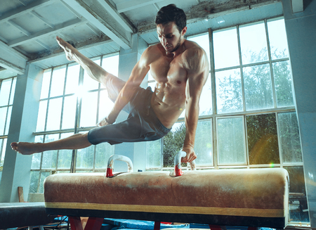 The sportsman performing difficult gymnastic exercise at gym. The sport, exercise, gymnast, health, training, athlete concept. Caucasian fit model Foto de archivo - 105869465