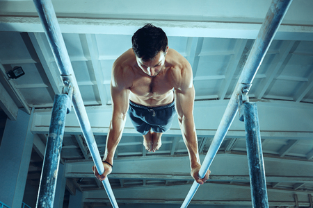 The sportsman performing difficult gymnastic exercise at gym. The sport, exercise, gymnast, health, training, athlete concept. Caucasian fit model Foto de archivo - 105869470