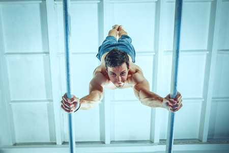 The sportsman performing difficult gymnastic exercise at gym. The sport, exercise, gymnast, health, training, athlete concept. Caucasian fit model Foto de archivo - 105869476