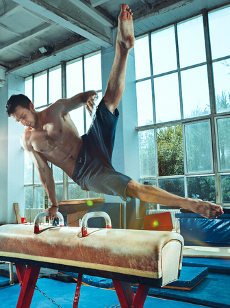 The sportsman performing difficult gymnastic exercise at gym. The sport, exercise, gymnast, health, training, athlete concept. Caucasian fit model Foto de archivo - 105869475