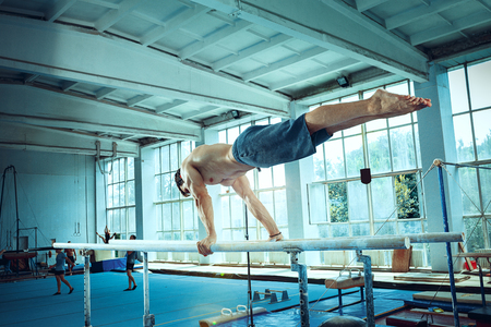 The sportsman performing difficult gymnastic exercise at gym. The sport, exercise, gymnast, health, training, athlete concept. Caucasian fit model Foto de archivo - 105869472