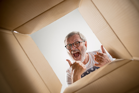 The surprised senior man unpacking, opening carton box and looking inside. The package, delivery, surprise, gift lifestyle concept. Human emotions and facial expressions concepts
