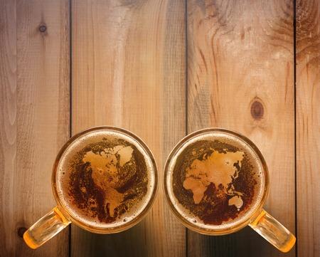 Widok z góry sylwetki mapy świata na piance w szklance piwa na drewnianym stole. Koncepcja narodowej miłości do piwa